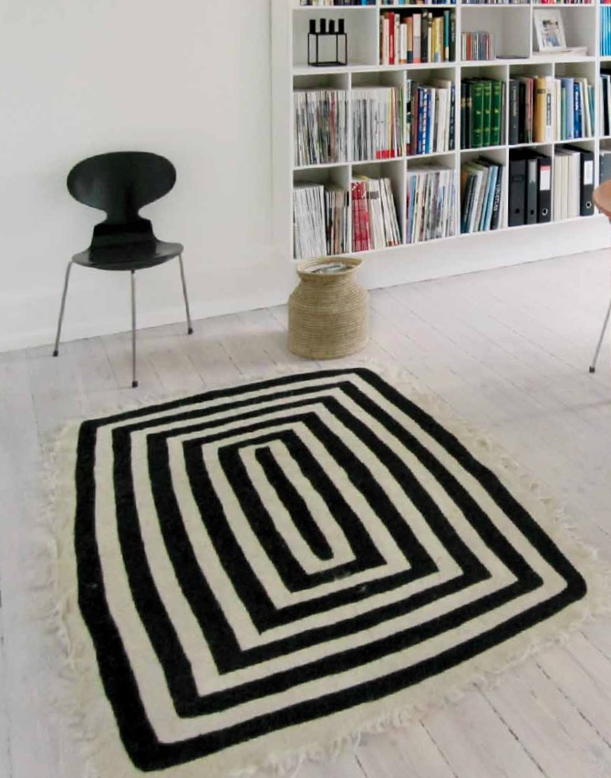 SQUARE CARPET, by TIKAU / Felted local wool (3 – 5 % cotton). / Colors: white/black / Size: 125 x 175 cm (size without the fringe) / Additional: Hand felted rug and hand embroidered black pattern.