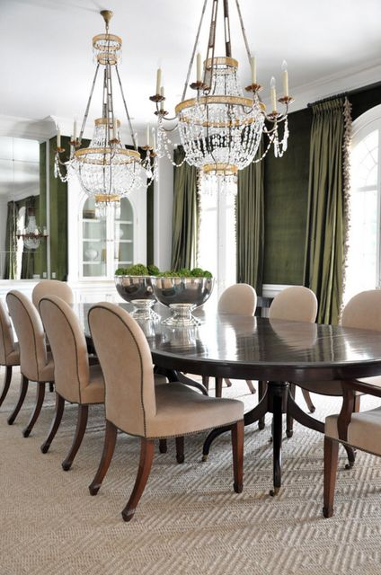 Crystal chandeliers deep olive green walls and matching curtains creates an elegant dining room