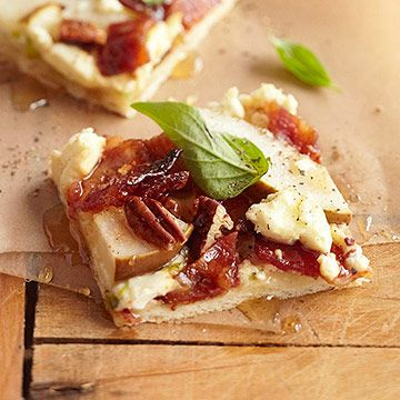 Top premade pizza crust with cream cheese, sliced pear, chopped pecans, feta cheese, and bacon.