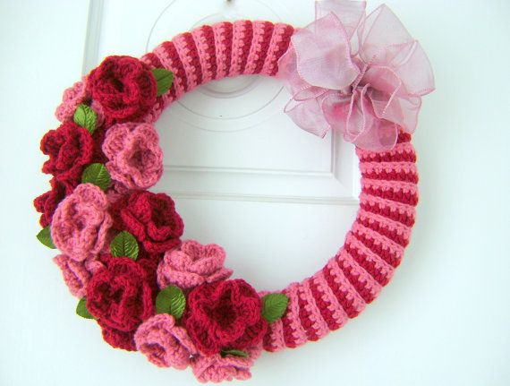 Made with worsted weight yarn, this wreath has a crocheted cover that is glued on. The roses are a deep red and a dusty rose in color. Small green leafs are in between the roses. A dusty rose wired bow completes the wreath.