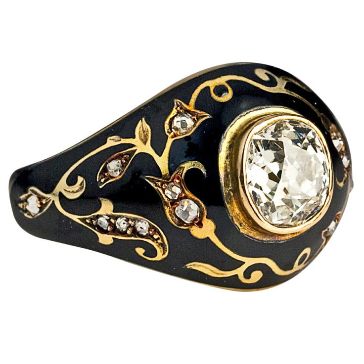 Russian, c. 1910  The 14K gold ring features an antique cushion cut diamond (6.4 x 6.2 x 3.8 mm, approximately 1.25 ct, K-L color, VS1 clarity) surrounded by scrolling gold foliage in oriental taste embellished with rose cut diamonds on a glossy black enamel ground.
