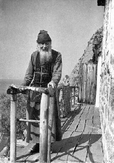 Hieroschemamonk Elder Theodosius    Builder of the Church of the Holy Trinity at Karoulia  (on Mount Athos).  Reposed in the sixty-ninth year from his birth, October 2/15, 1937.   Here seen standing upright on the narrow porch of his cell.  Notice behind him the vertical cliffs of Karoulia on which this Elder chose to live his life.