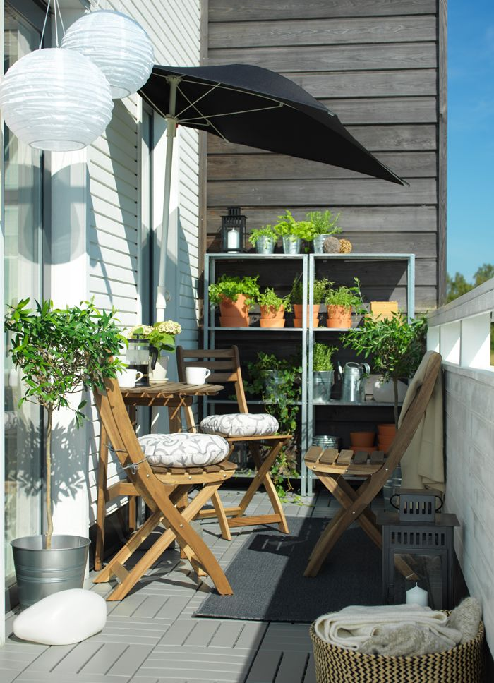 A narrow balcony with a wooden table and chairs in the sun. Shelves with rows of plants can be seen behind.