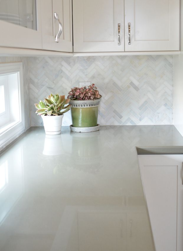 White cabinets with marble herringbone backsplash and sage green quartz countertops