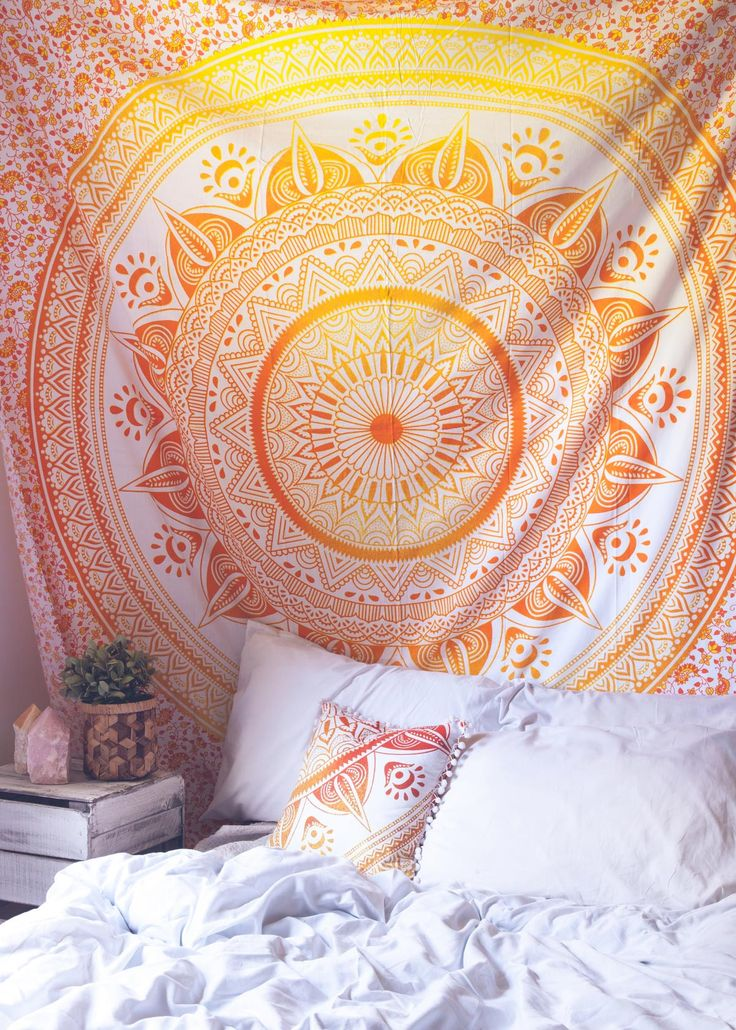 Top off your bed or accent a wall with this unique boho tapestry, featuring a bold orange and yellow mandala pattern on soft white fabric. This tapestry also doubles as a picnic blanket, perfect for f