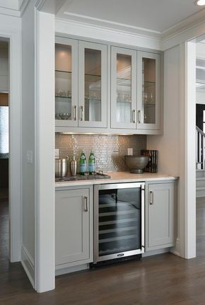 Contemporary living room bar nook is filled with gray glass front upper cabinets and gray shaker lower cabinets fitted with a glass front wine cooler paired with a white marble countertop and a gray glass linear tile backsplash.