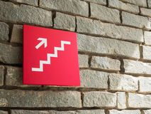 Red stairs going up sign on wall brick Stock Photos