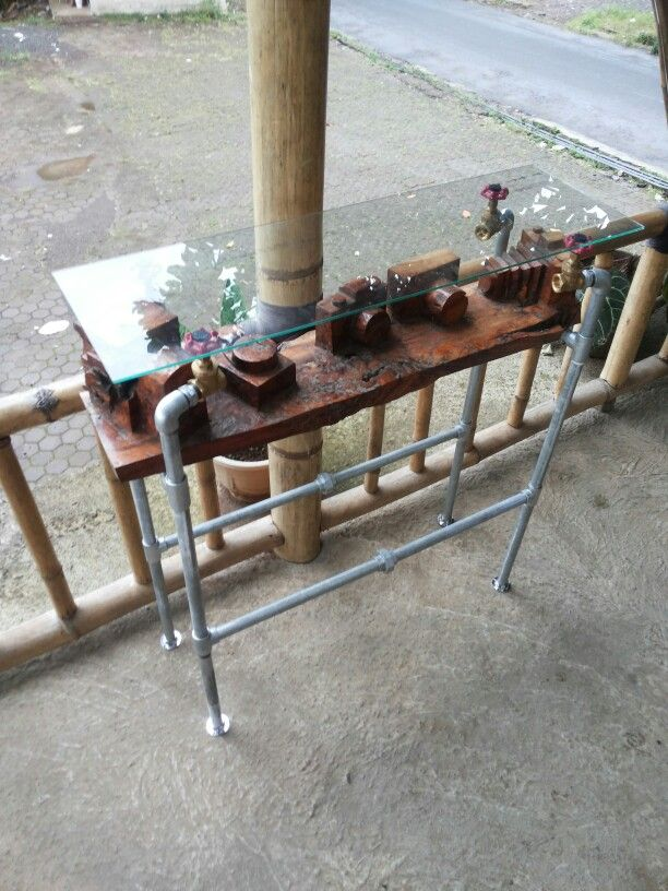 Carved wooden table with plumb pipe