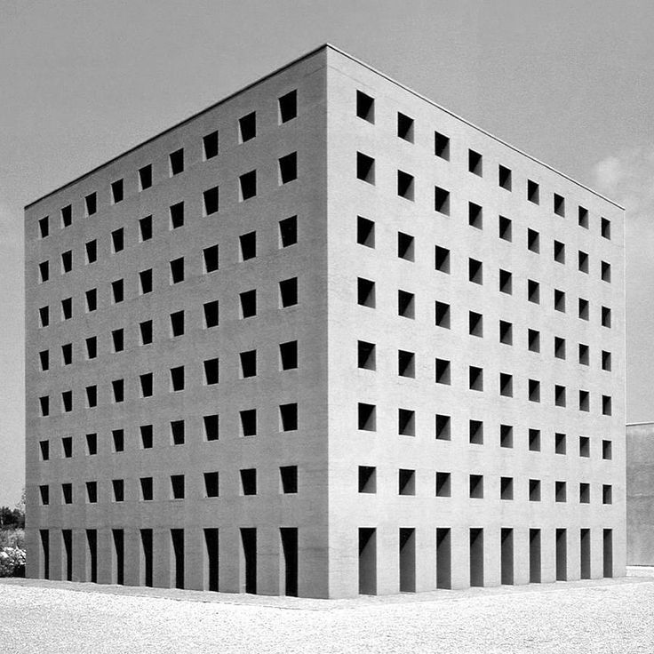 """Aldo Rossi's unfinished San Cataldo Cemetery in Modena, Italy, is considered one of the first and most important Postmodern buildings. Rossi once declared that """"I cannot be Postmodern, as I have never been Modern,"""" yet his cemetery for Modena displays the strong colouring, bold form and historically referential detailing that became synonymous with the movement."""