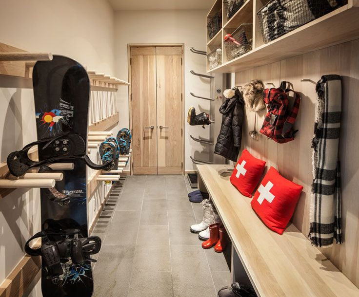 This mudroom (or winter sport storage space) is perfectly designed with light wood cabinets, racks and hooks. A wood bench makes it easy to take off boots, and upper storage spaces with wire baskets keep things organized.