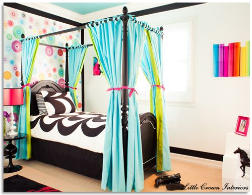 Colorful bedroom for a girl by Little Crown Interiors - featuring bright spiral wallpaper, acrylic wall art, black canopy bed and funky black and white bedding.