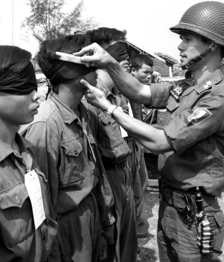 Robert Kersey ©Stars and Stripes Gio Linh, South Vietnam, March, 1967: A South Vietnamese soldier combs the hair of bound and blindfolded North Vietnamese Army prisoners in preparation for the arrival of Premier Nguyen Cao Ky. During his visit to the camp near the DMZ, Ky talked with the now-well-groomed POWs; he also signed two leaflets and a 175mm round which were fired toward North Vietnam by U.S. and ARVN artillery units.
