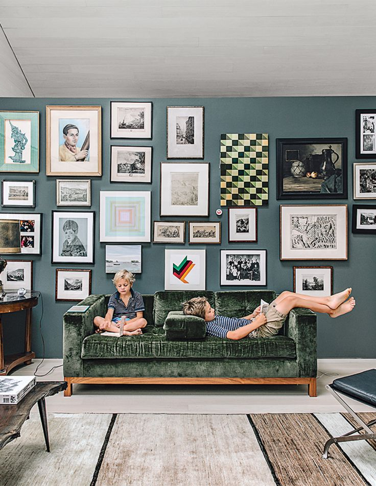 In the playroom, a velvet Desiron sofa is set off by Down Pipe paint from Farrow & Ball.