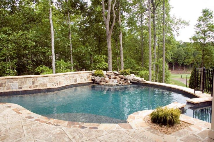 ~ The natural materials chosen for this swimming pool and hot tub harmonize with the surrounding landscape ~ A rustic waterfall is the perfect focal point for this gorgeous outdoor space ~