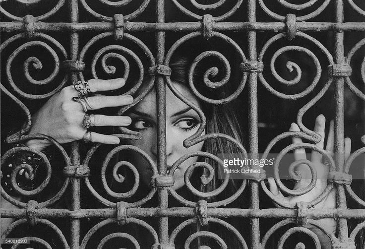 Socialite Talitha Getty (aka Mrs. Paul Getty, Jr.) looks through an iron grille at the Palais de la Zahia near her Marrakech, Morocco home. January 15, 1970 License VOGUE