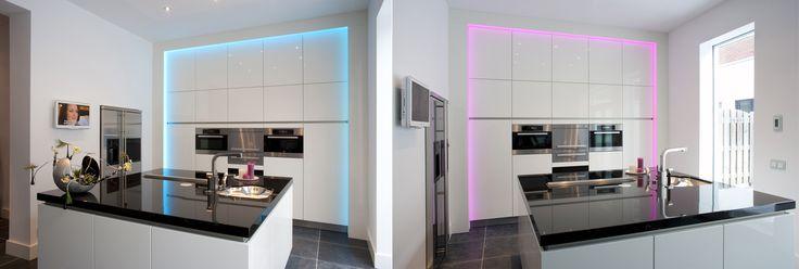 Maatwerk keuken met kookeiland. Blad in zwart graniet. Apparatenwand in hoogglans wit spuitwerk met RGB LED kader