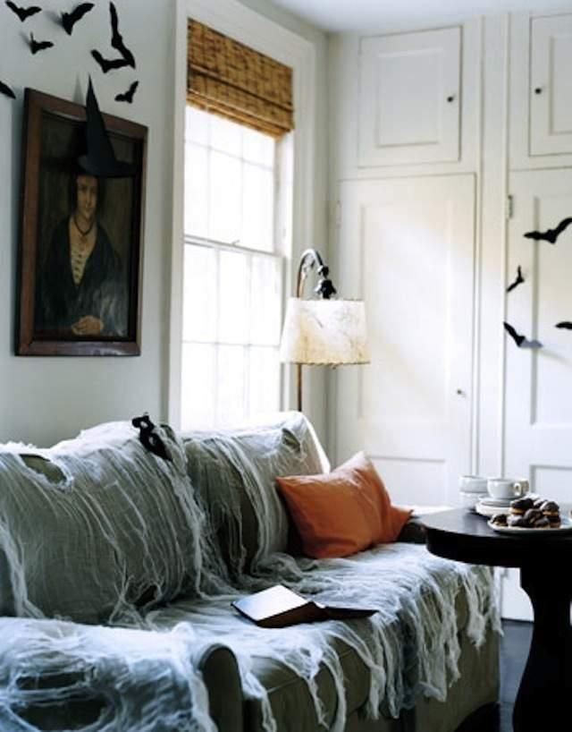 DIY: Last-Minute Halloween Decor : cheesecloth draped over couch for spiderweb effect