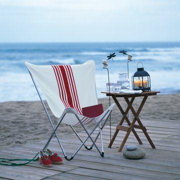 un fauteuil pop up de chez Lafuma en toile blanche, personnalisé avec des galons rouges cousus en rayures basque sur la toile blanche. Pour un transat dété.