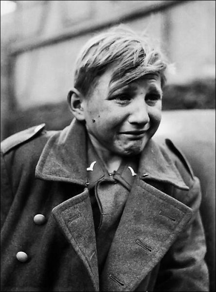 This terrified young German boy is a possible Allied prisoner towards the end of WWII. Dressed in a barely used uniform and coat, new enough that the creases are still crisp, he like so many other children, suffered the consequences of adult political decisions.  from Child soldiers in World War II