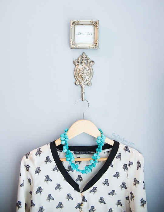 If there's no space for shelving, you could still put a pretty hook on the inside of your door for planning the next day's outfit.