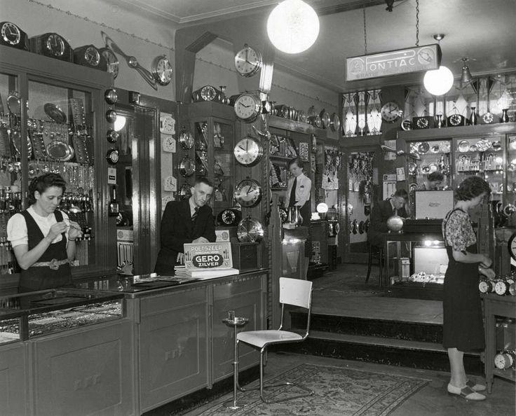 Interieur van klokkenwinkel in Rotterdam, met vele klokken en ook zilverwaar in de winkel. Nederland, 1940.
