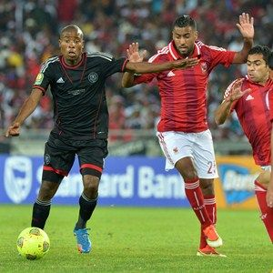 Orlando Pirates' Thabo Matlaba (L) escapes with the ball during the African Champions League first leg final between South Africa's Orlando Pirates and Egypt's Al-Ahly