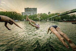 Three members of the outdoor swimming gang dive into the canal in east Paris at sunset. Of course, it can be dangerous but we are adults and informed so we swim at our own risk.