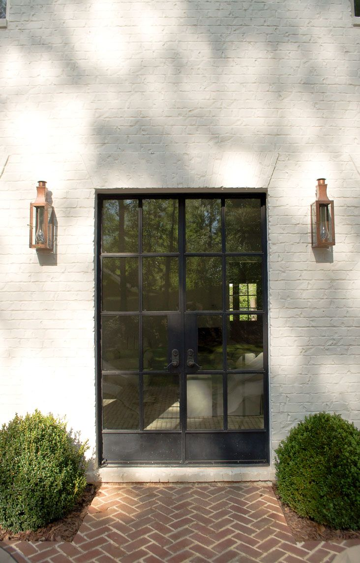 metal doors in black, herringbone brick and boxwood