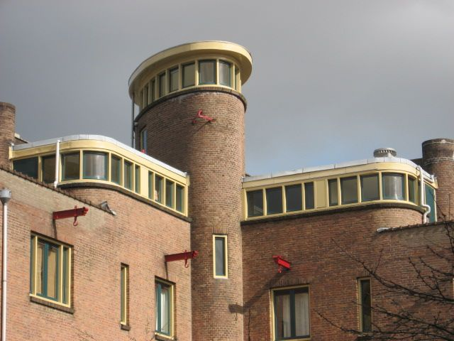 Woningcomplex van Van Epen, met verticale elementen, geel-groene raamkozijnen, en geaccentueerde hijsbalken (Saffierstraat 61, Amsterdam)