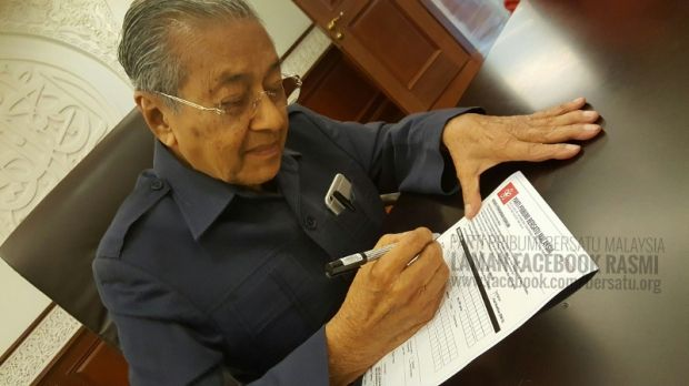 Tun Dr Mahathir Mohamad filling an application form to sign up as the first…