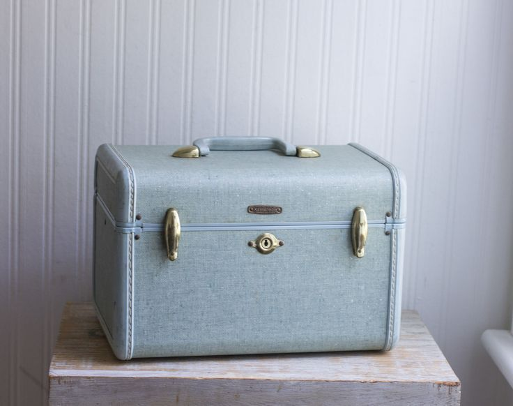This blue Samsonite train case is mid century vintage. A pretty dusty blue with faint white speckles, it has gold metal accents and white seam stitching. This hard travel case or carry on is perfect f