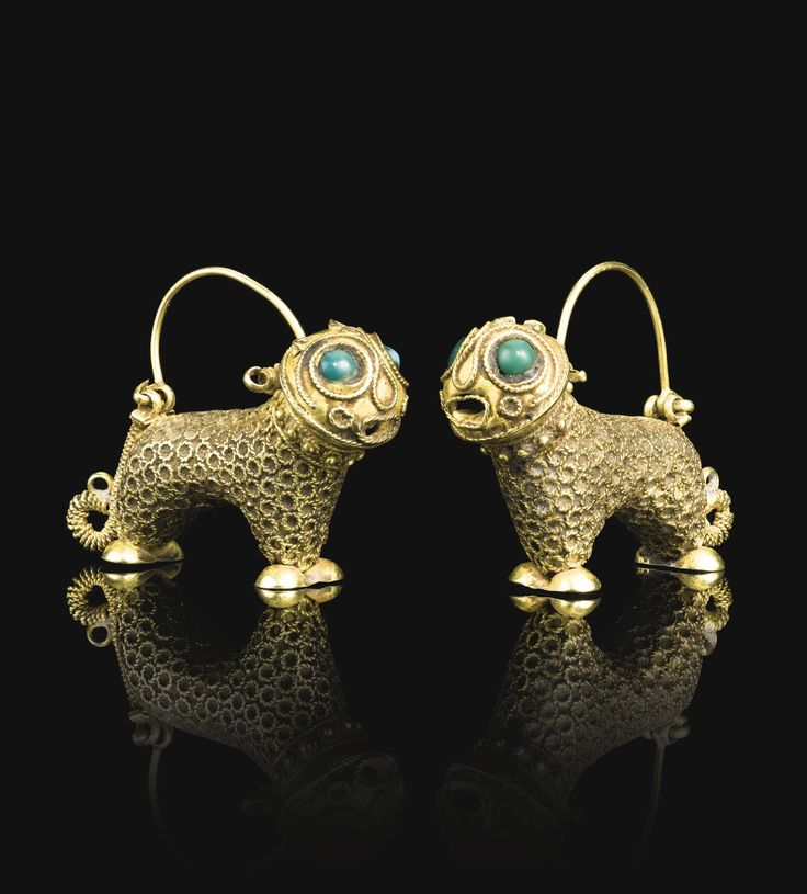 A PAIR OF LION-FORM GOLD EARRINGS, PERSIA, 12TH CENTURY each composed of gold, hammered and chased, designed as stylised lions decorated with twisted wire and inset green and turquoise stone eyes