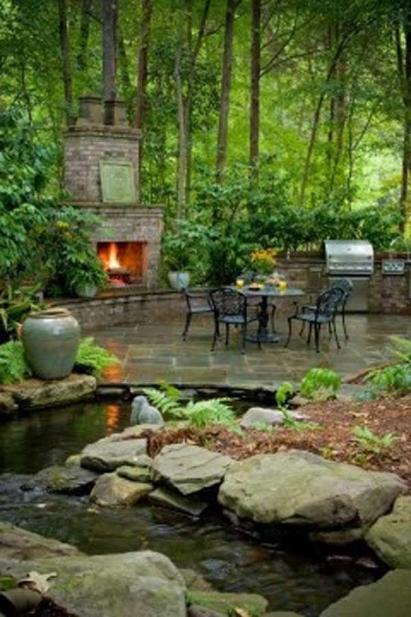 wooded garden surrounds patio with a fireplace