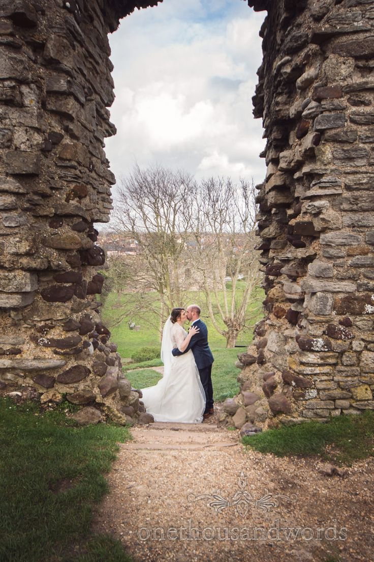 Bride and groom kiss between the walls of ruins of Christchurch Castle in Dorset.  Photography by one thousand words wedding photographers