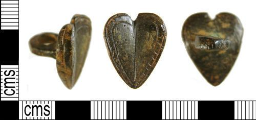 A Medieval/ Post-Medieval copper alloy button in the form of a heart, with both halves of the face obliquely-angled forward towards thickened sides (max.4.48mm thick) from a deep groove at the centre (1.54mm thick).   The face is decorated with randomly placed tiny circular punch marks on each face and a double groove flanking the edge, filled with equally interspersed transverse grooves. Around the thickened edges is a central groove with transverse grooves across it. To the reverse…
