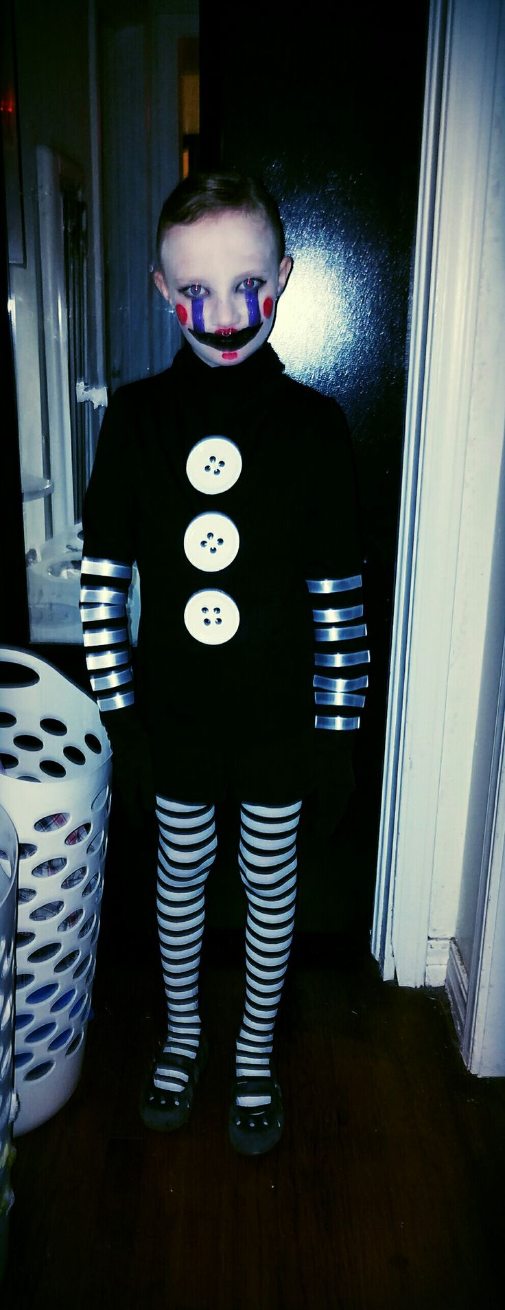 Five Nights at Freddy's Marionette costume! Buttons made out of painted jar lids and used iron on adhesive and white ribbon for the stripes on arms of a black turtle neck shirt. Add face paint and done! Spoooky!!