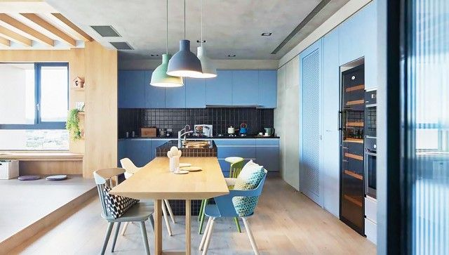 Kitchen with pastel colored cabinents and a mod wooden table