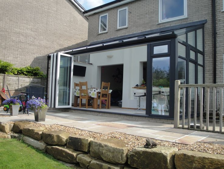 A Conservatory Transformation Dark grey lean-to conservatory including Pilaster posts, bi-folding doors and high performance glass – Refurbish My Conservatory