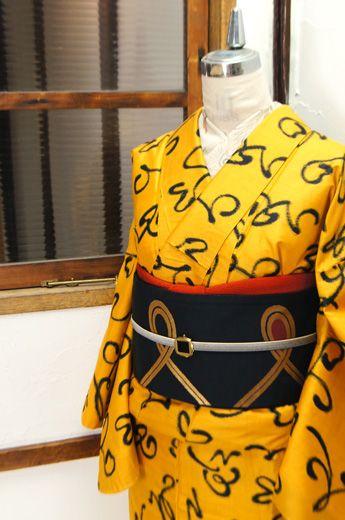 クロムイエローに近いオレンジで織り出されたカリグラフィーのような抽象パターンが印象的な銘仙の袷着物です。