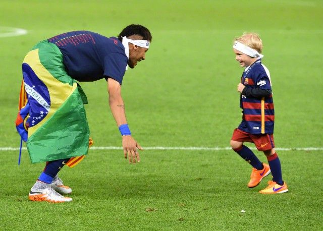 Neymar Jr and his son David Lucca da Silva Santos celebrate the victory after the UEFA Champions League Final between Juventus Turin and FC Barcelona at Olympiastadion on June 6, 2015 in Berlin