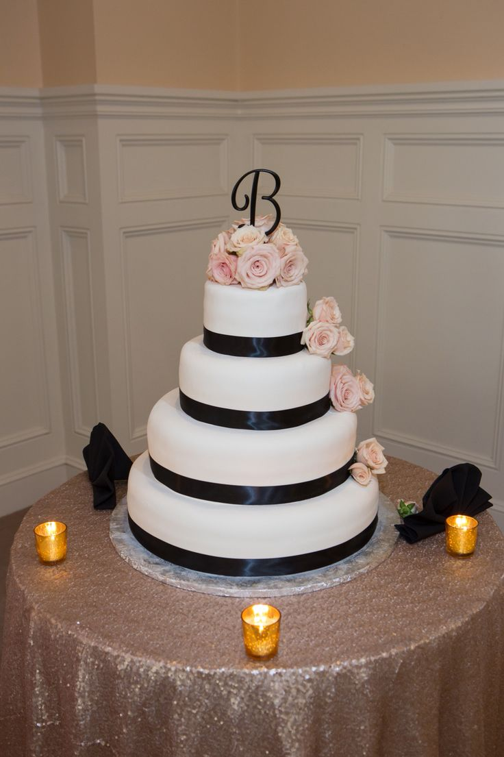 I absolutely loved our wedding cake. my florist surprised me by using the sahara roses and making them into somewhat of a cake topper. she went above and beyond on everything she did. / black monogram cake topper. round 4 tier ivory wedding cake with black ribbon. champagne sequin table linen. gold mercury candle votives. sahara roses. blush, champagne and ivory wedding with black and gold accents.