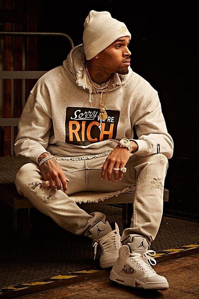 Chris Brown wearing  Joyrich Sorry We're Rich Sweater, Cartier 22Ct Diamond Roadster XL W62019X6 White Dial Stainless Steel Watch, Harold Kensington Jumper, Jordan Supreme x Air Jordan 5 Retro, Bape Sta Knit Beanie