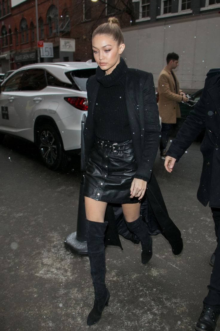February 15, 2016 Hadid looked sleek in the snow donning an all-black ensemble of a turtleneck, leather mini and thigh high boots.