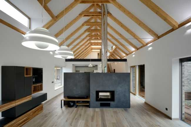 Obytná část je rozdělena polovysokou stěnou s krbem na část obývací a jídelnu