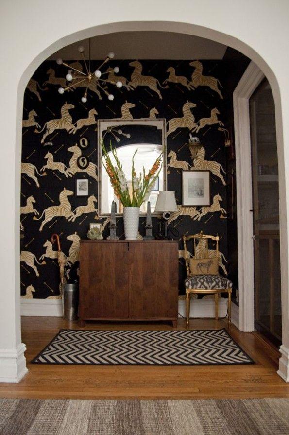 Black Scalamandre Zebras wallpaper with sputnik light and warm wood cabinet
