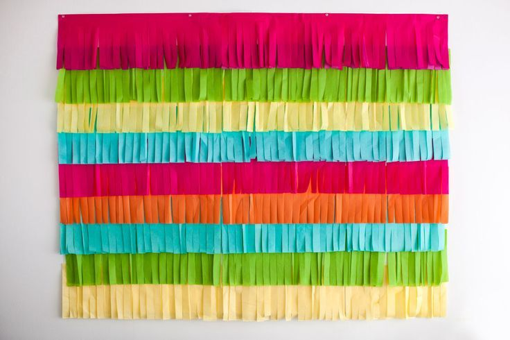 All you need is colorful tissue paper, poster board, scissors, packing tape + push pins to make a festive fringe photo booth backdrop for your Cinco de Mayo party.