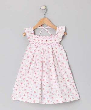 This pretty dress shows off dainty angel sleeves, smocking and a sweet floral print. The look is classic, charming and cute as a button.