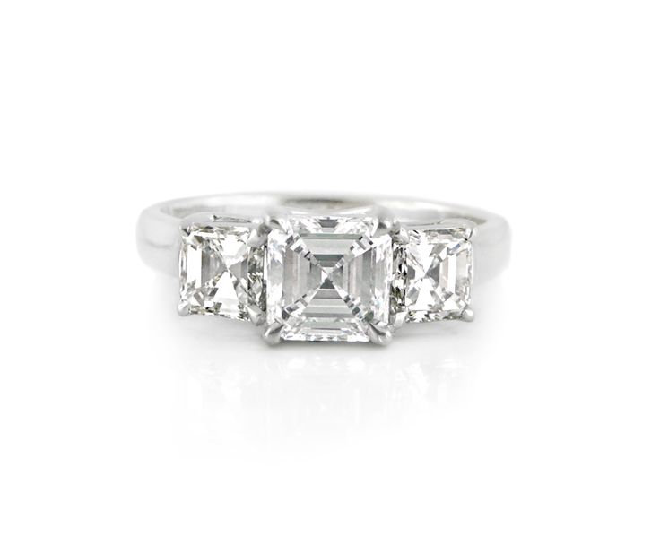 An 18ct White Gold and Square Emerald Cut Three Stone Ring