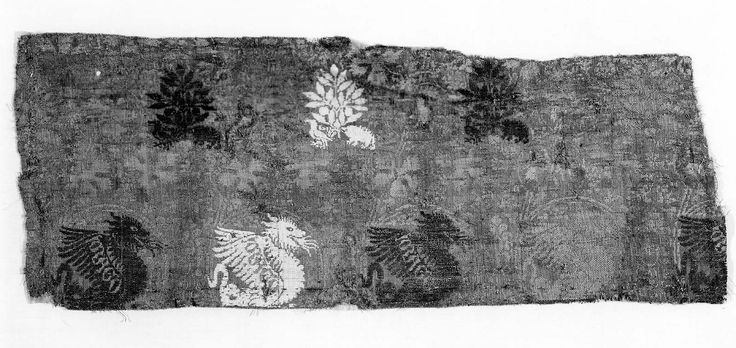 Italian second half of 14th century. Fragment of salmon silk self-patterned with vine, brocaded with green and white silk and gold-metallic thread with dragons (wings are inscribed with DRAGO) above rows of trees with small animal and birds under each tree.