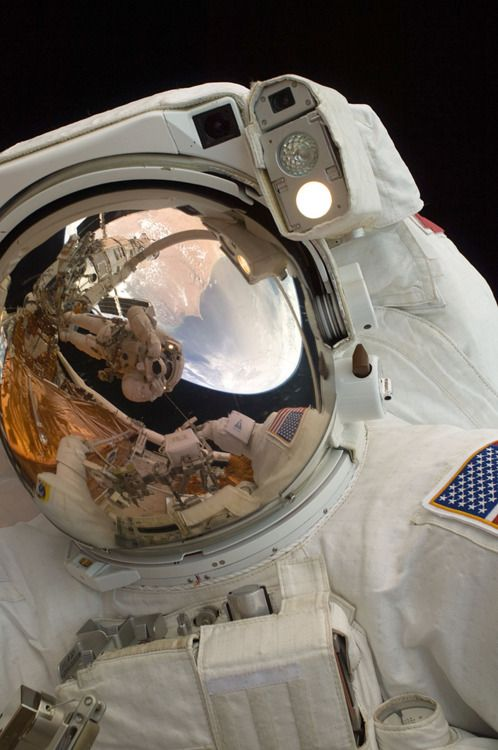 A close-up of Astronaut John Grunsfeld shows the reflection of Astronaut Andrew Feustel, perched on the robotic arm and taking the photo.